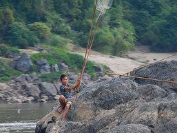 Boy fishing the Mekong River, Laos